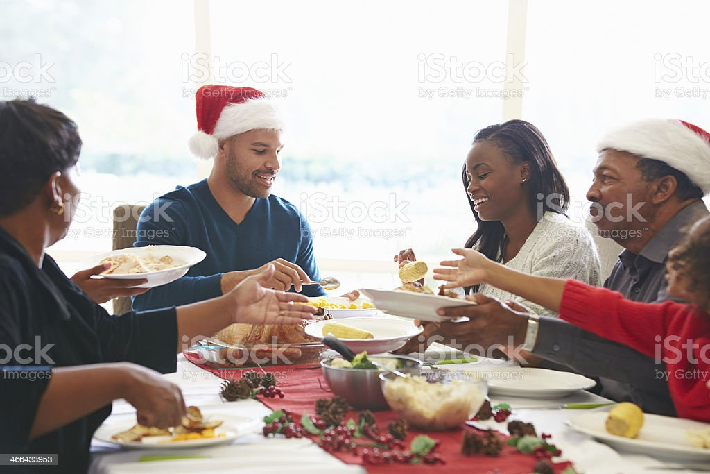 Multi Generation Family Enjoying Christmas Meal At Home On Christmas...