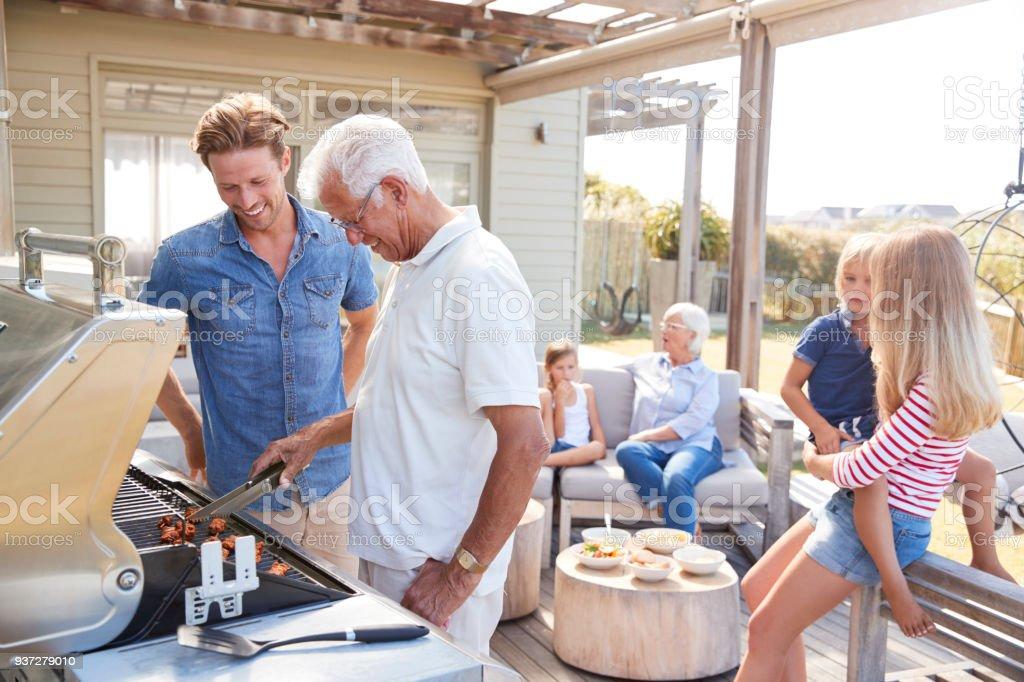 Multi génération famille appréciant cuisine Barbecue à la maison - Photo