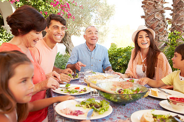 multi generation family enjoying meal on terrace together - spanish food stock photos and pictures