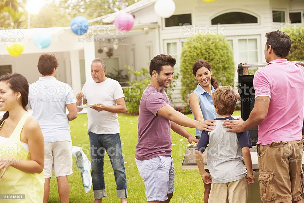 Multi Generation Family Enjoying Party In Garden Together stock photo