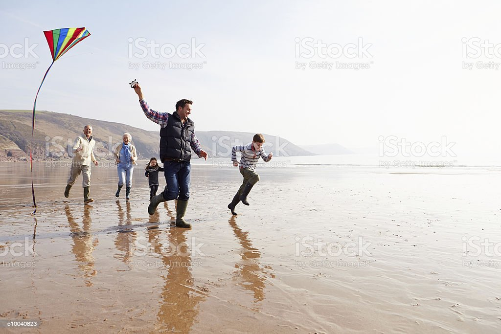 Multi-generazione famiglia volo aquilone sulla spiaggia d'inverno - foto stock