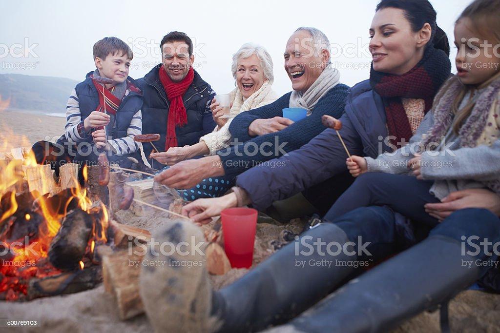 Multi Generation Family Having Barbeque On Winter Beach stock photo