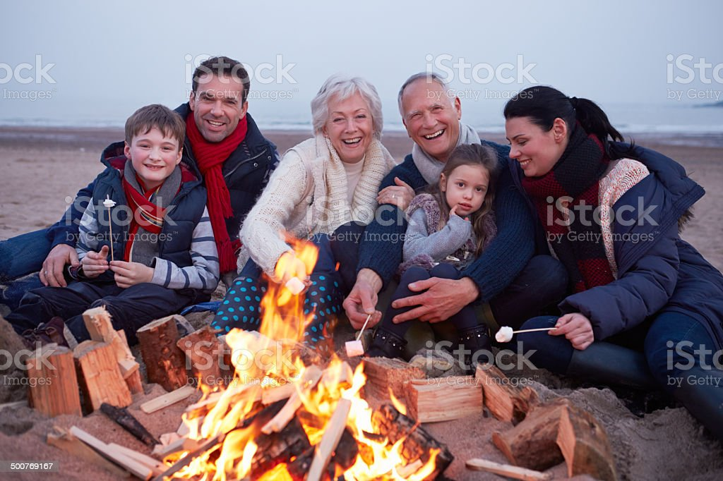 Multi Generation Family Having Barbeque On Winter Beach stock photo