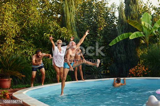 Multi generation family having fun on the pool in back yard. Jumping in to the pool from poolside and enjoying the summer time