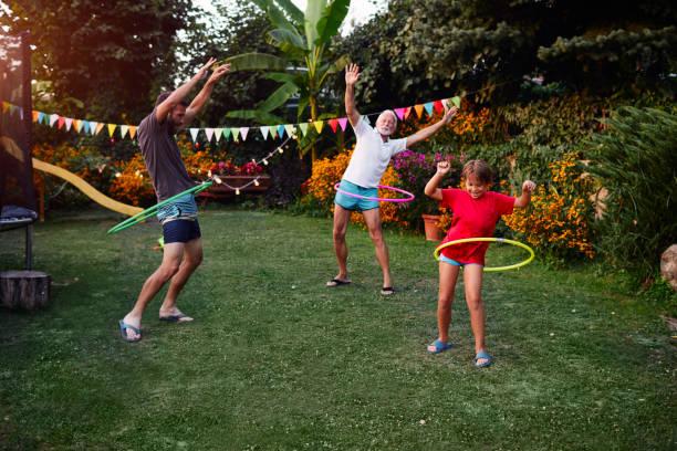 multi-generation familie hula hooping in hinterhof - kinderparty spiele stock-fotos und bilder