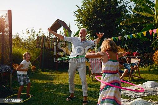 Multi generation family hula hooping in backyard. Senior man with grandchildren having fun outdoors.