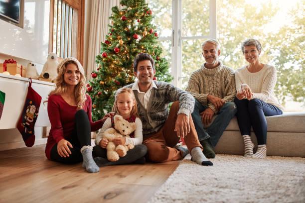 multi-generationen-familie vor weihnachtsbaum - alte weihnachtsbäume stock-fotos und bilder