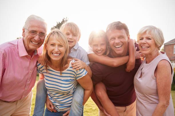 カメラに笑顔を庭で多世代家族をクローズ アップ - 祖父母 ストックフォトと画像
