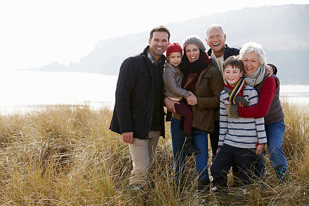 multi generation family in sand dunes on winter beach - multi generation family stock photos and pictures