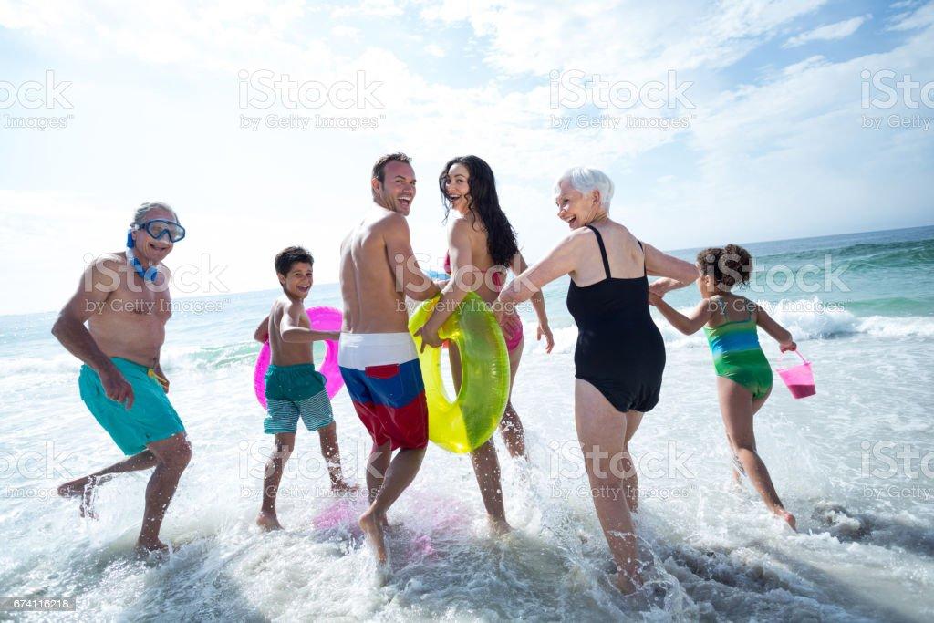 多代家庭在海灘笑運行 免版稅 stock photo