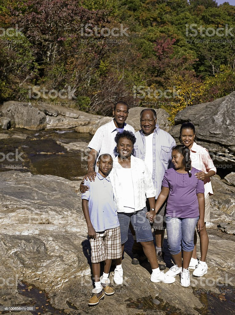 Multi generation family on tucks at stream, smiling foto de stock libre de derechos