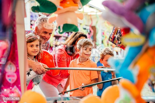 Grandparents helping their grandchildren hook a duck on a side show at a fairground