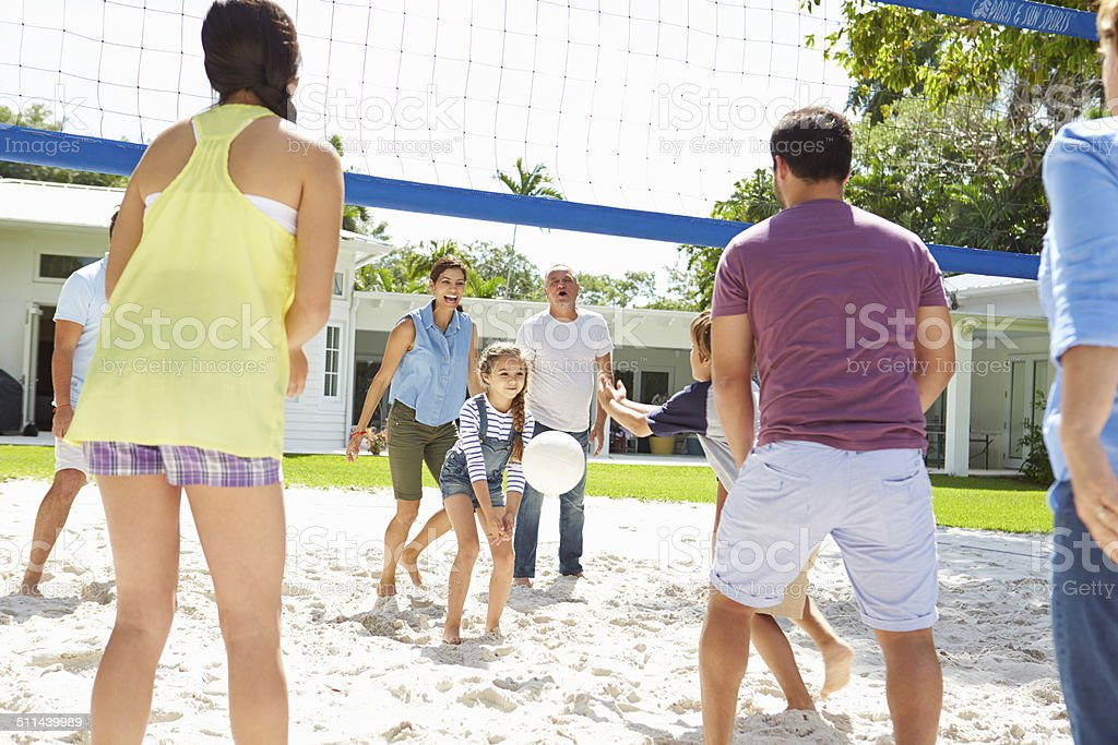 Multi Generation Family Playing Volleyball In Garden stock photo