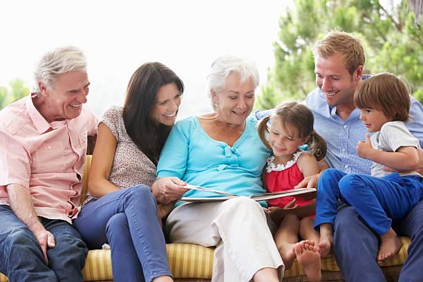 multi-generationen-familie liest ein buch auf garten sitz - storytelling fotos stock-fotos und bilder