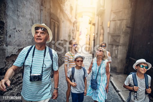 Multi generation family enjoying summer vacations. The family is walking in the narrow streets of a beautiful Italian town.  Nikon D850