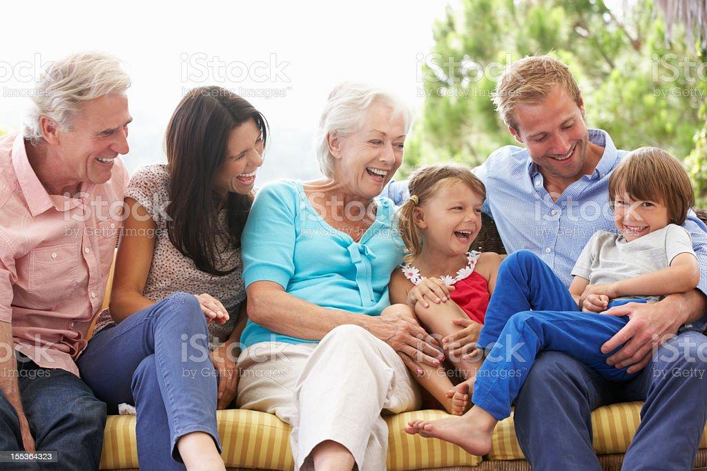 Multi Generation Family Sitting On Garden Seat stock photo