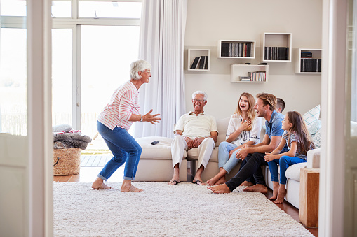 istock Multi Generation Family Sitting On Sofa At Home Playing Charades 937278692