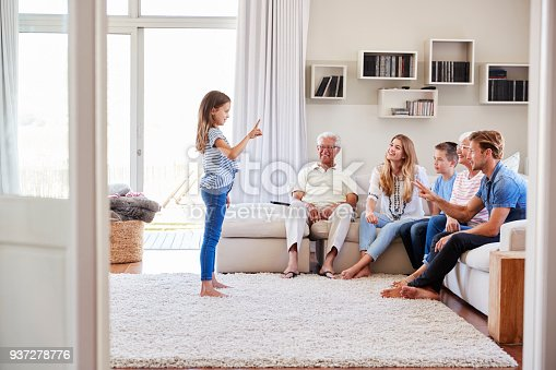 istock Multi Generation Family Sitting On Sofa At Home Playing Charades 937278776