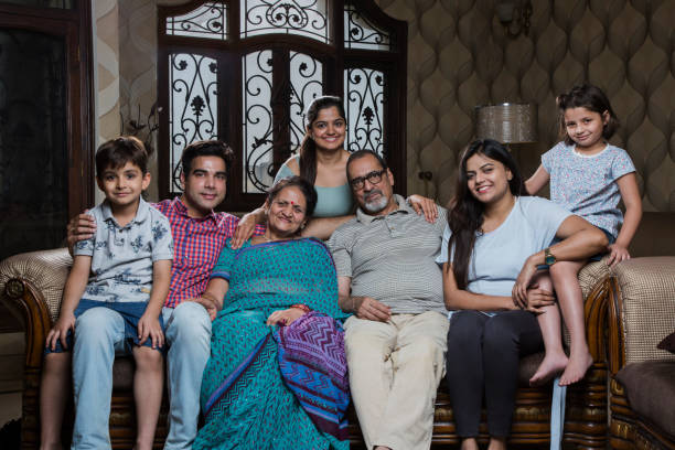 Multi generation family sitting on sofa in living room - Stock image Family, Senior Adult, Child, Grandfather, Caucasian Ethnicity indian family stock pictures, royalty-free photos & images