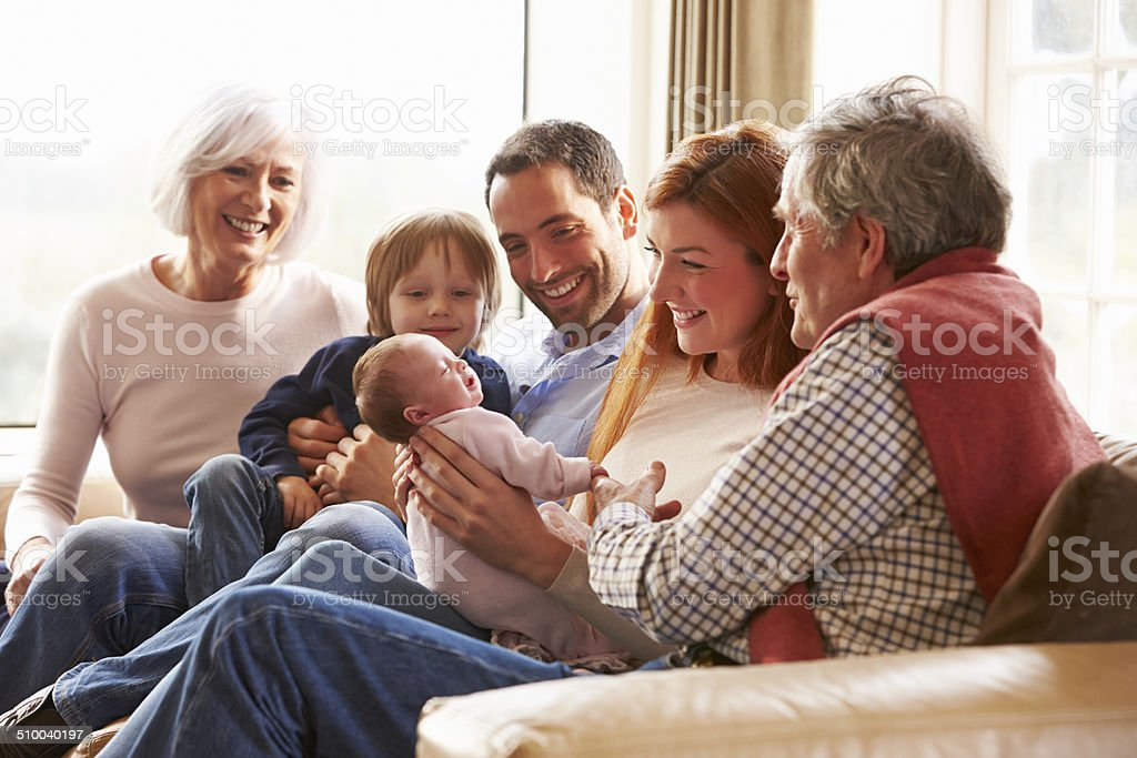 Multi Generation Family Sitting On Sofa With Newborn Baby stock photo