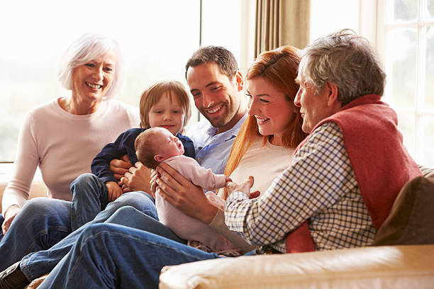 Várias gerações de família sentada no sofá com o bebê recém-nascido - foto de acervo
