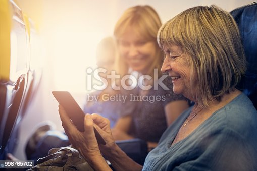 Senior woman, her daughter and grandson are travelling by plane. The grandmother is reading ebook. Family having fun during the flight. Nikon D850