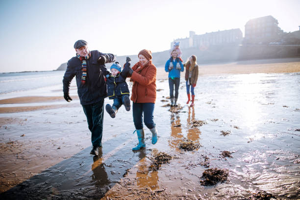 Multi- Generation Family Walking Along the Beach Three generation family enjoying walking along the coast. Its cold outside so they are wrapped up warm. Grandparents swinging the little boy northeastern england stock pictures, royalty-free photos & images