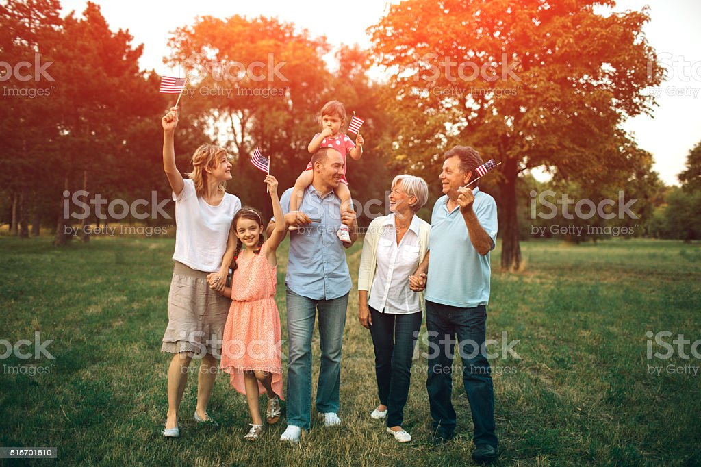 Multi generation Family Walking In A Park With US Flags. stock photo