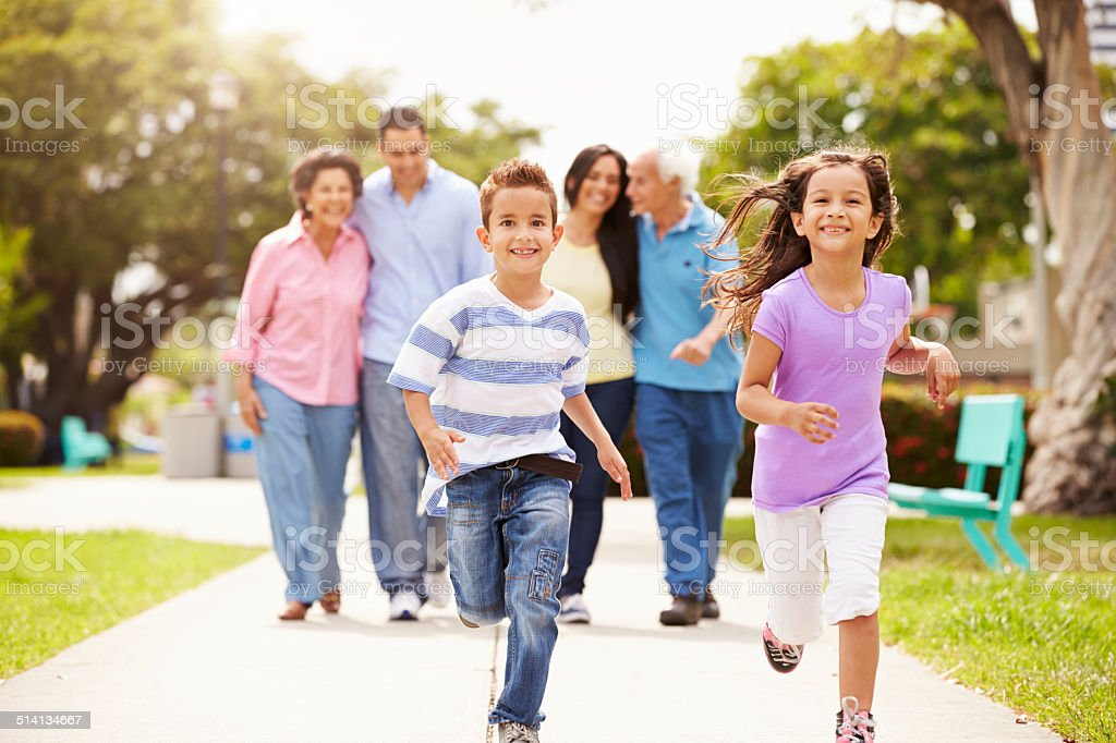 Multi Generation Family Walking In Park Together stock photo
