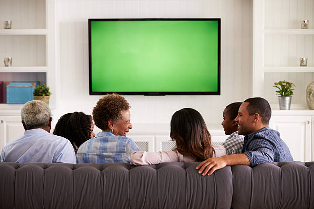 multi generation family watching tv and laughing, back view - family watching tv stock photos and pictures