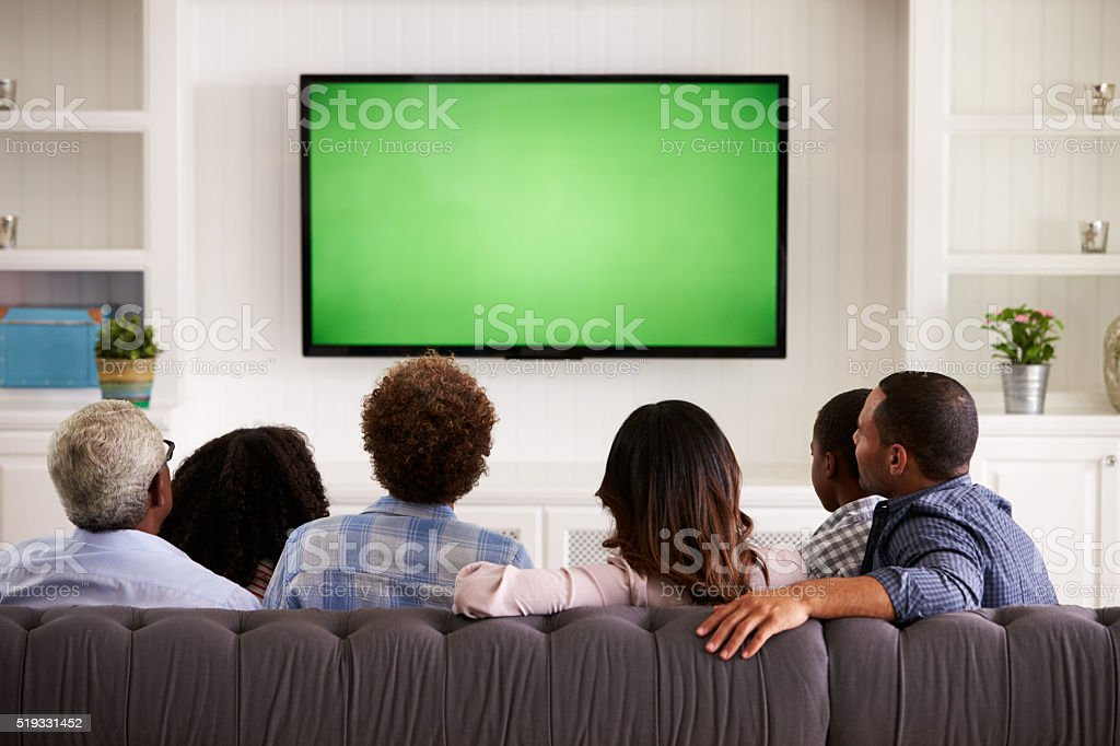 Multi generation family watching TV at home, back view stock photo