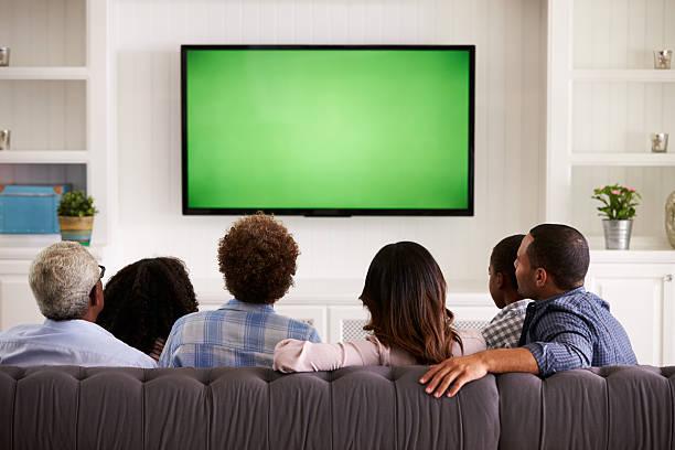 multi generazione famiglia guardando la tv a casa, vista posteriore - industria televisiva foto e immagini stock