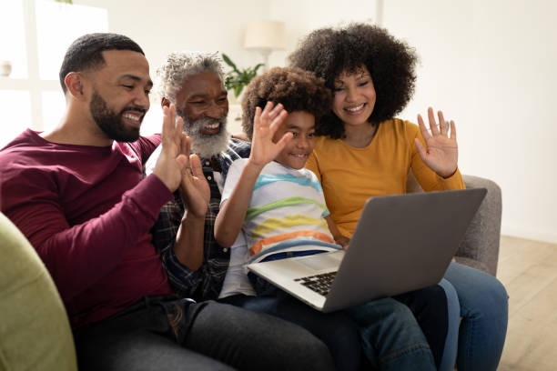 Multi generation family waving while having a video call on laptop at home stock photo