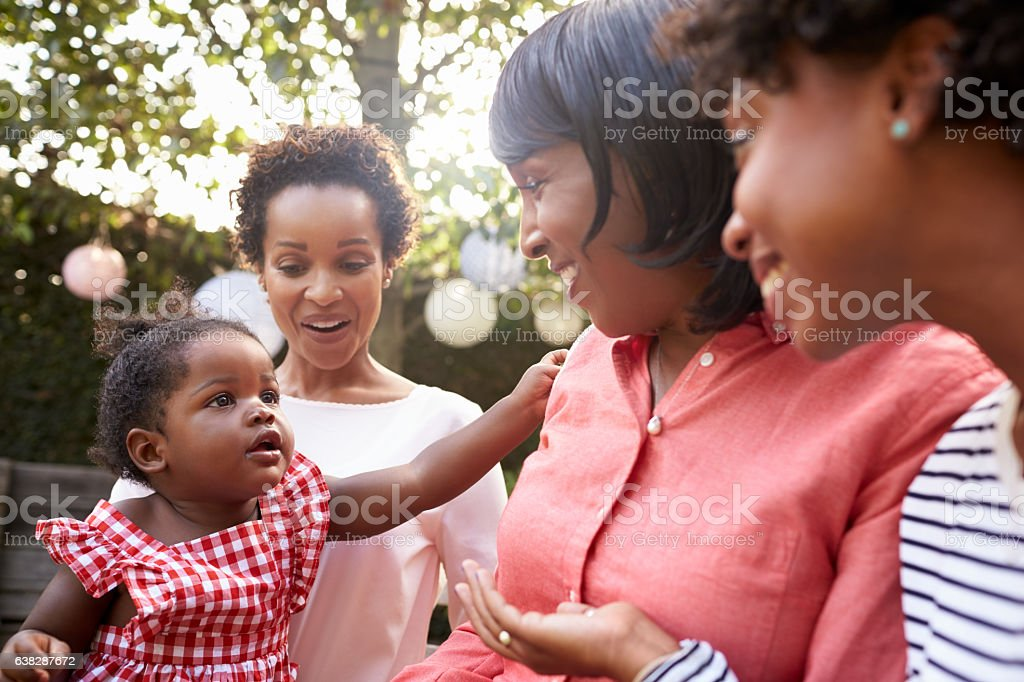 Multi generation female family members gathered in a garden stock photo