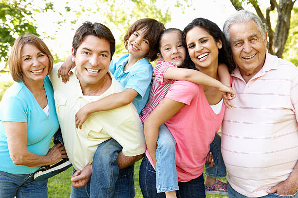 Multi Generation Hispanic Family Having Fun In Park stock photo