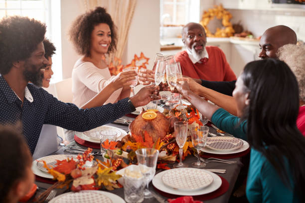 multi generation mixed race family raise their glasses to make a toast at their thanksgiving dinner table - thanksgiving стоковые фото и изображения
