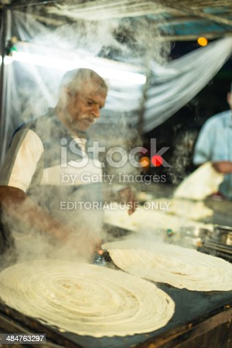 Cochin, India - December 23, 2013: Old man cooks masala dosas on a big stove in an open market in the night in Cochin. The smoke is rising over the man.