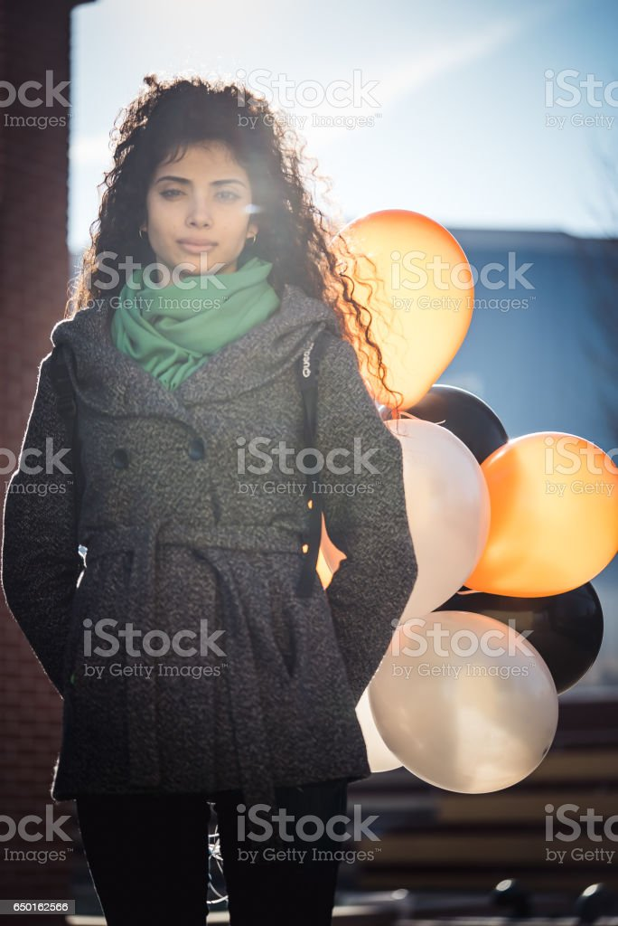 Multi raced girl with tricolor helium balloons stock photo