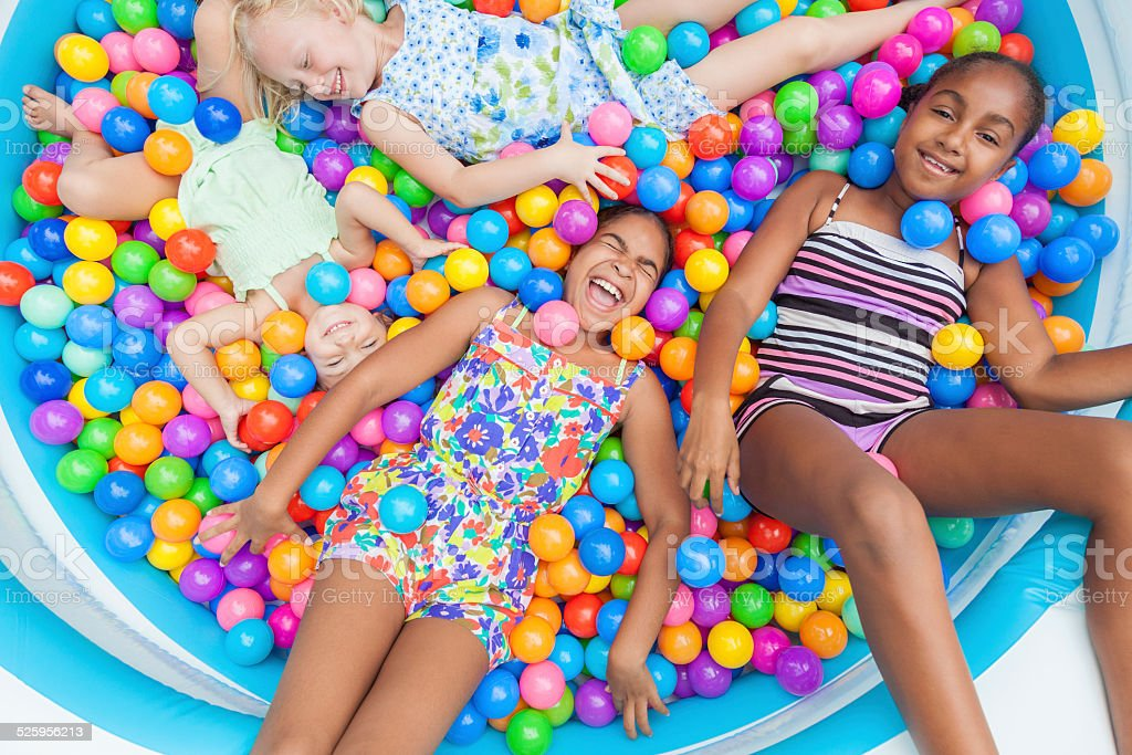 Multi Racial Girls Children Fun Playing in Colored Ball Pit stock photo