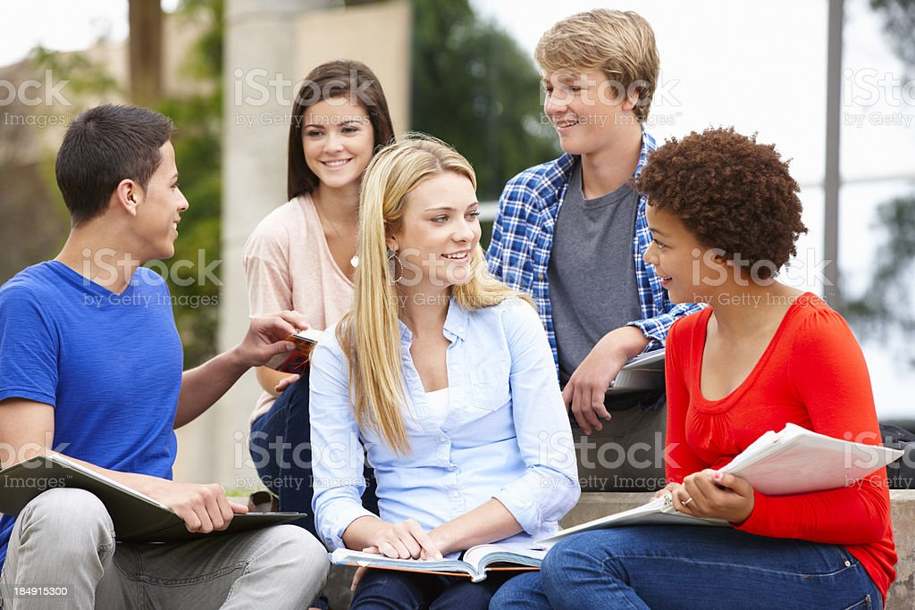 Multi racial student group sitting outdoors royalty-free stock photo