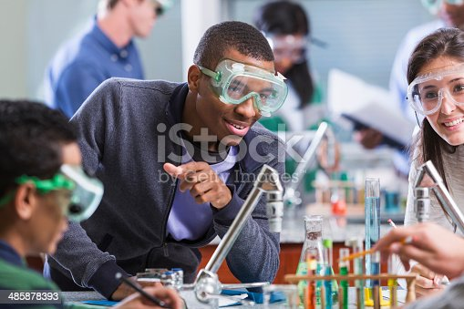 129300487 istock photo Multi racial students in chemistry class wearing safety glasses 485878393