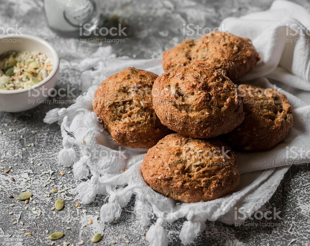 Multi seeds whole wheat buns on a grey stone background. stock photo