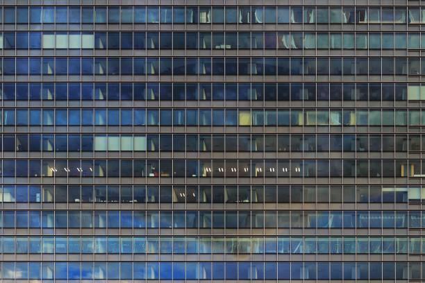multi-etagen-glas verkleidung fassade bürogebäude. lichtdurchlässige äußere metall aluminium-rahmen reflektieren himmel und beleuchteten raum im inneren. geschäftsturm arbeitsplatz. - fassadenschnitt stock-fotos und bilder