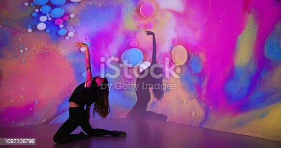 Multicolor background projection upon a female dancer.