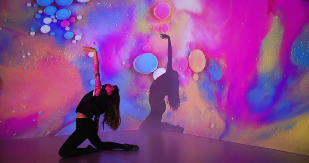 Multicolor background projection upon a female dancer stock photo