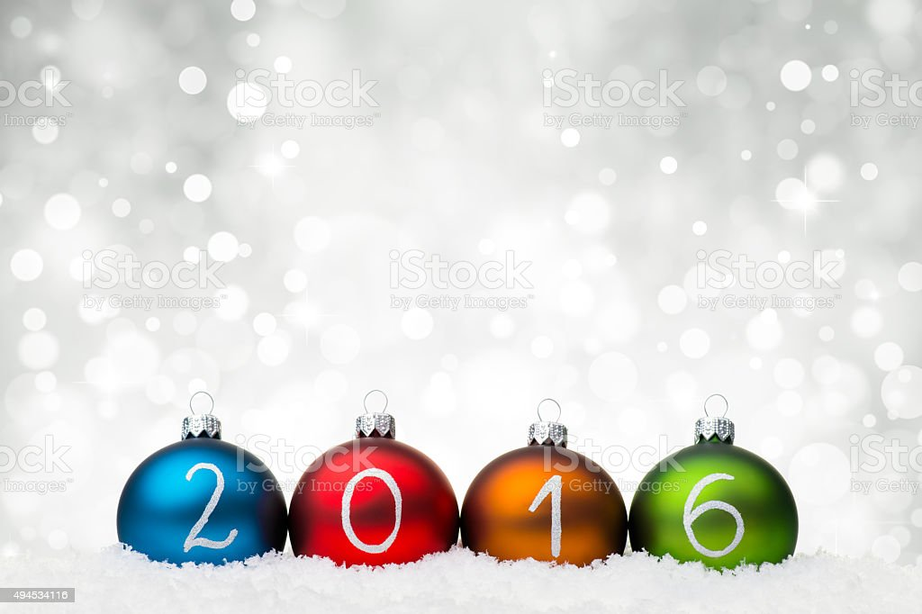 Multicolor Baubles arranged in 2016 year on snow stock photo