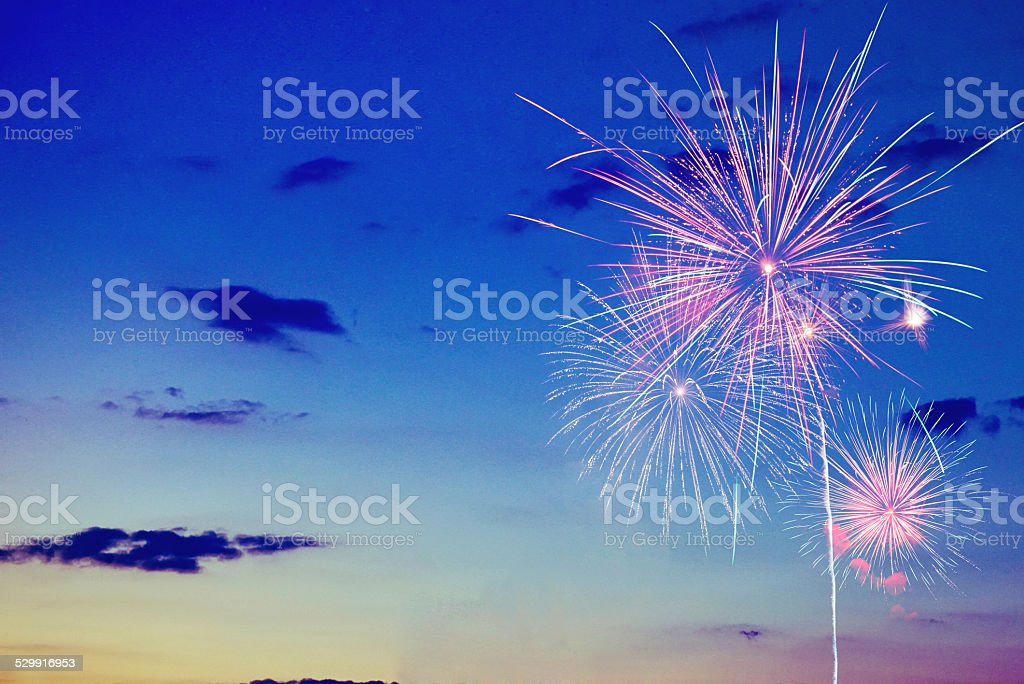 Multicolor bursting fireworks against a sun setting sky stock photo
