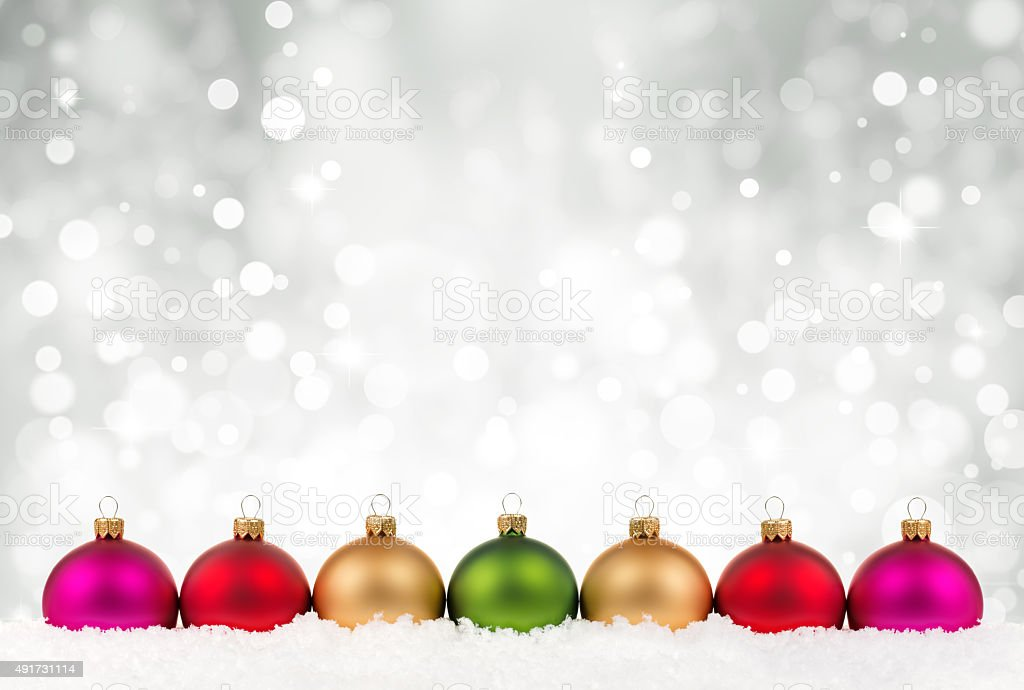 Multicolor clean baubles in line on  snow stock photo
