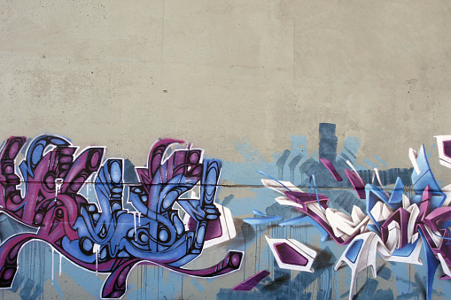Multicolor Graffiti painted on a cement wall background.  Those illegal graffitis are often found under highway concrete structure or any other abandoned places.