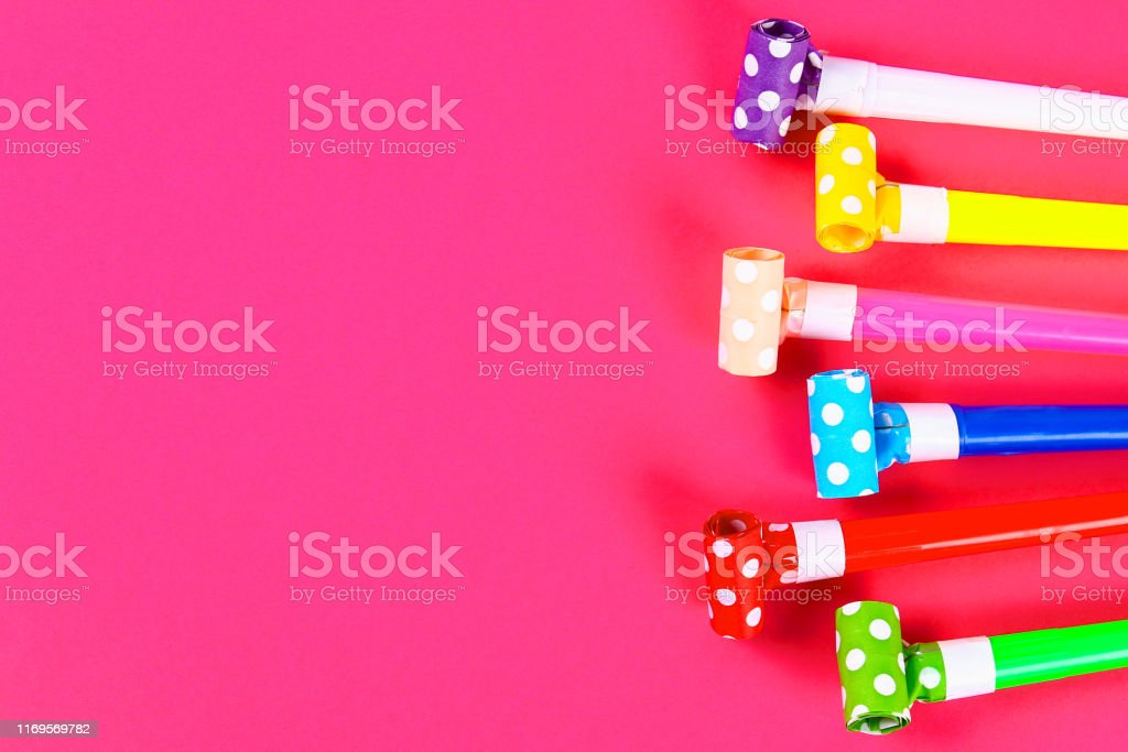Multicolor party blowers on pink background. Multicolored party...
